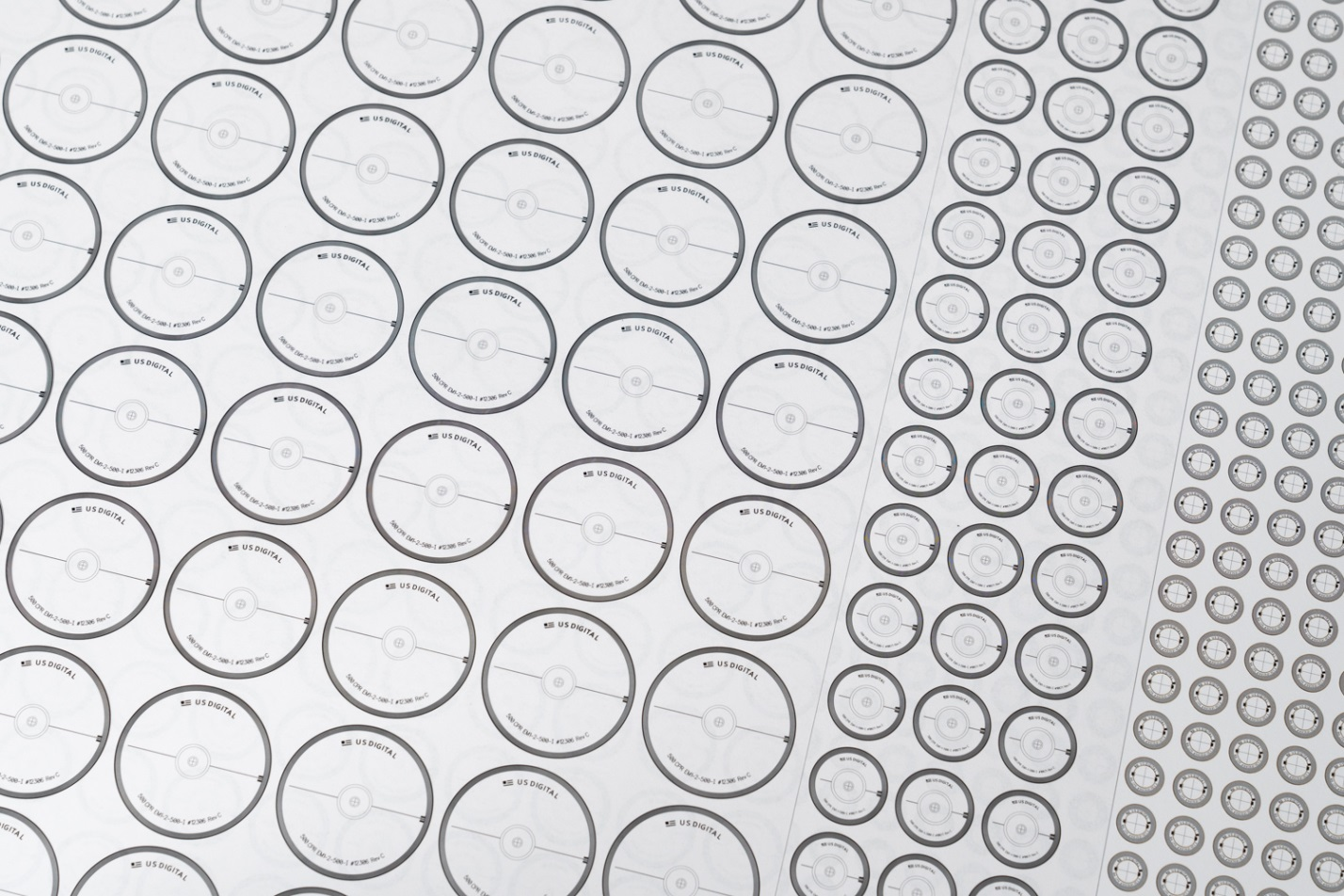 Disks are imaged on sheets of Mylar film, then separated from each other by a laser cutter. Shown above are 2-inch, 1 inch, and 1/2-inch encoder disks (50.8 mm, 25.4 mm, 12.7 mm).