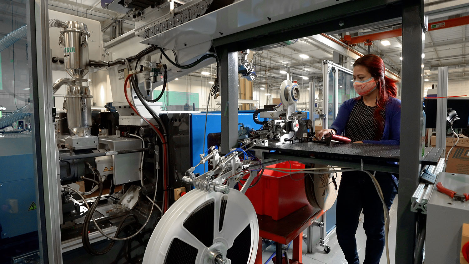 US Digital Mechanical Engineer Camilla Garcia works a new machine she designed in the injection molding area.